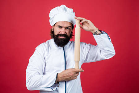 confident chef guy with beard and moustache in cook uniform hold rolling pin, kitchen utensil Standard-Bild