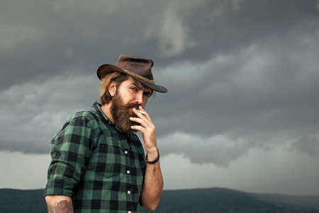 bearded man. texas brutal cowboy. brutal hipster with moustache in hat. fashion model wear casual west clothes. male beauty standard. looking so trendy. Confident and handsome man. Country music