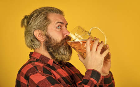 drink your beer. trying a new beer. brutal hipster drink beer. mature bearded man hold beer glass. mug of alcohol beverage. confident bartender. barman in bar. resting at pub. Cheers. sport bar Stock fotó