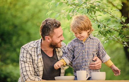 Happy family love. Child development. happy fathers day. Little boy with dad outdoor. childhood happiness. healthy food and dieting. Family day. son and father eating milk porridge