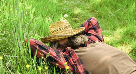 Agriculture farmer rest after day work. Worker in rural farm. farmer relax on green grass. Ecology concept. Green field in summer. Countryman on green meadow. protect green environment
