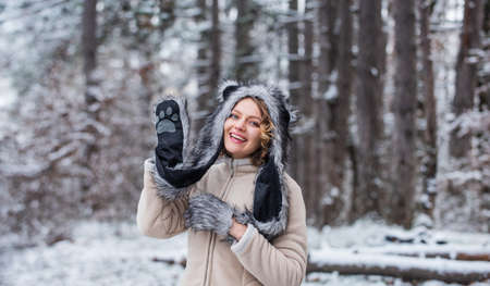 Heartwarming concept. Animal care. Winter themed portrait cosy outfit. Woman wear wolf hat. Animal rights. Wild life symbol. Girl in snowy forest. Faux fur animal hat perfect for fantasy theme Stock fotó