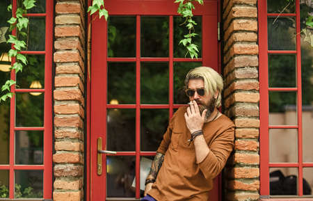 Cool guy relaxing. Went on smoke break. Hipster smoking irish pub entrance background. Smoking habit. Brutal guy sunglasses smoking tobacco. Smoking outdoors. Fashionable mature man with cigarette