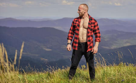 Man stand top mountain landscape background. Athlete guy relax mountains. Beautiful environment. Muscular tourist walk mountain hill. Hiker muscular torso reach mountain peak. Hiking concept