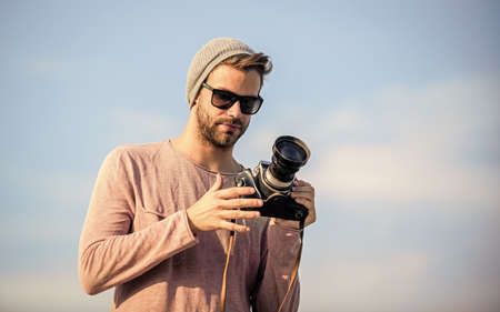 Hipster reporter taking photo. Guy photographer outdoors sky background. Handsome photographer guy retro camera. Manual settings. Photojournalist concept. Travel blogger. Professional photographer Stock fotó