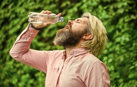 Another sip. Handsome Man Drinking Fresh Water From bottle. Morning routine. Daily intake of water. Thirsty male model enjoying refreshing drink. Healthy eating and drink. Drinking water