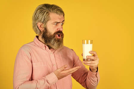 Healthy food. Drink protein cocktail. Lactose free. Emotional bearded man hold glass of milk. Pasteurized milk. Vegan milk concept. Vegan milks made from wide variety of beans nut, seeds and grains