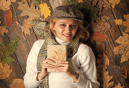autumn female fashion. she love reading. woman hold maple leaf. canada. girl relax on autumn background. Beauty in autumn style. book of nature. Staying beautiful any season Stock fotó