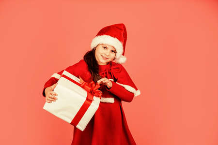 Little secret. merry christmas. xmas joy mood. small santa kid pink background. little girl present box. winter holiday shopping. time for presents. gift brings joy and happiness. happy new year