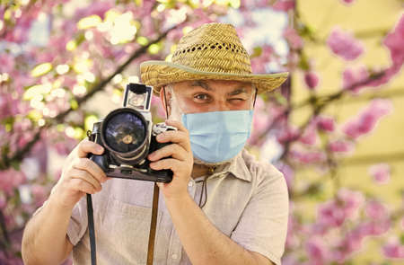 Pandemic concept. Risky photographer. Keep working. Pollen allergy. Tourist camera photo. Nature photography. Senior man respirator mask. Professional photographer work during coronavirus quarantine