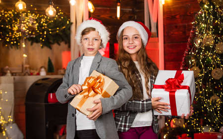 Winter shopping. Loving family with presents in room. brother and sister in santa hat. children happy time. Merry Christmas Happy Holidays. exchanging gifts at decorated christmas tree. New Year 2020 Stock fotó