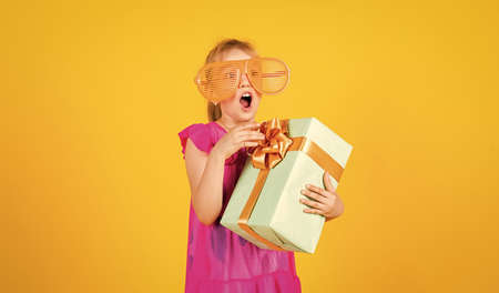 gift of surprise. its shopping time. small girl hold present box. little kid with gift box. happy birthday party. childhood happiness. lets celebrate holiday. child in summer day on yellow background
