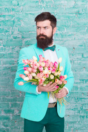 We take flowers personally. Spring gift. Bearded man hipster with flowers. Love. international holiday. Womens day. March 8. Bearded man with tulip spring bouquet. Spring time. enjoying spring