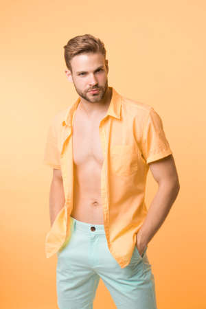 Want to see torso. It is hot here. I will show you my body. Man handsome bearded guy undressing yellow background. Guy confident attractive macho feels while unbuttoning shirt