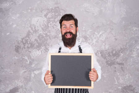 mature guy with beard and moustache is professional chef demonstrate cooking menu in cafe on empty chalkboard, cooking food Standard-Bild
