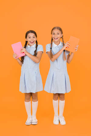 Book store concept. vintage kid fashion. back to school. small girls hold workbook and notepad. encyclopedia book for children. small girls love read. old school. surprised friends in retro uniform