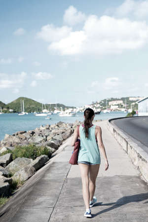 Sexy woman walk along sea in st.thomas, british virgin island. Woman in top and shorts on sea side promenade on sunny day, back view, beach fashion. Summer vacation on island, wanderlust