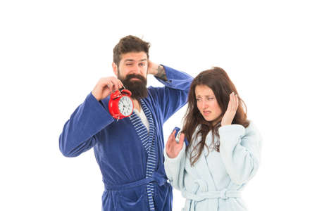 A sleepy morning. Couple in love waking up in morning. Pretty woman and bearded man holding alarm clock early in the morning. Sexy girlfriend and brutal hipster wearing nightrobes in morning Standard-Bild