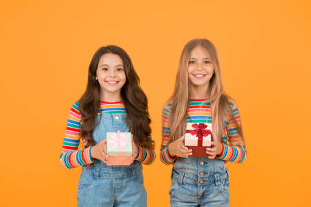 Being thankful for everything. Thankful for every gift of fate. Teaching kids be thankful. Children hold gift boxes yellow background. Kids delighted gifts. Girls celebrate holiday. Happy friends