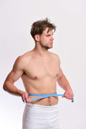 Man with blue measuring tape around naked torso Stock fotó