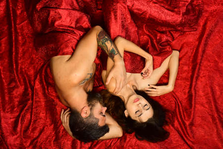 Couple in love lies on red sheets. Man and woman Stock fotó