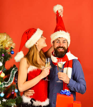 Mister and Missis Claus hold glasses of champagne.