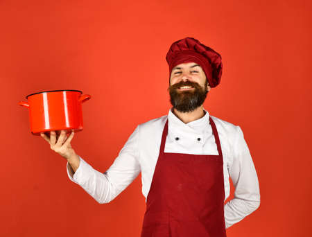 Man with beard holds kitchenware on red background.