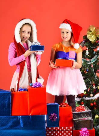 Kids in Santa costumes with gift boxes and packages