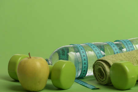 Dumbbells in green color, water bottle, measure tape, towel, fruit Stock fotó