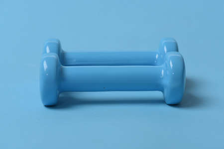 Dumbbells made of blue plastic on blue background Stock fotó