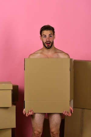 Macho with beard and surprised face covering himself with box Stock fotó