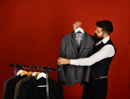 Shop assistant or seller holds grey suit on clothes hanger