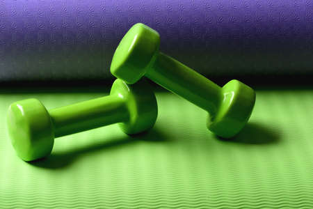 Barbells lying on yoga mat, close up. Sports and health