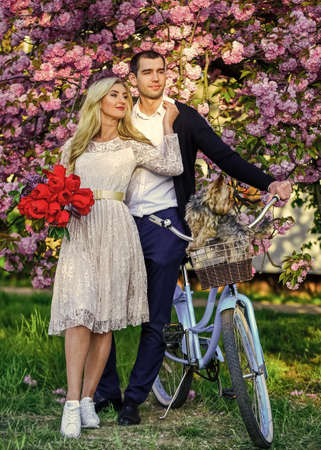 man and woman in park  pink blossom. beauty and fashion.