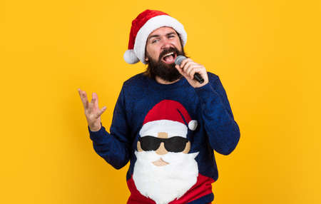 christmas music. bearded mature man wear knitted sweater sing in microphone.