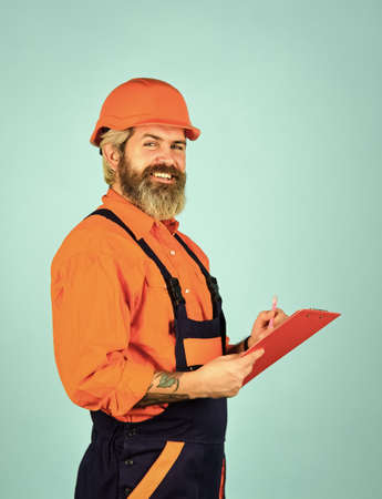 Checklist. Inspecting. Control concept. Foreman with document. Delivering building materials. Man in hard hat holding clipboard looking information. Buy materials for renovation. Bearded storekeeper