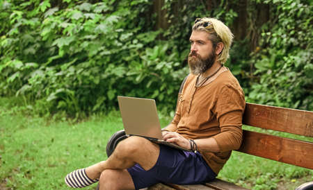 Homeschooling concept. online distant education. hipster inspired work in park. agile business. mature student working on computer. go shopping on cyber monday. bearded man sit on bench with laptop 版權商用圖片