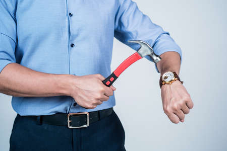 Dear stress, lets break up. Manager cropped view crash wrist watch with hammer. Time break. Time-break. Deadline and punctuality. Handling stress at work Banco de Imagens