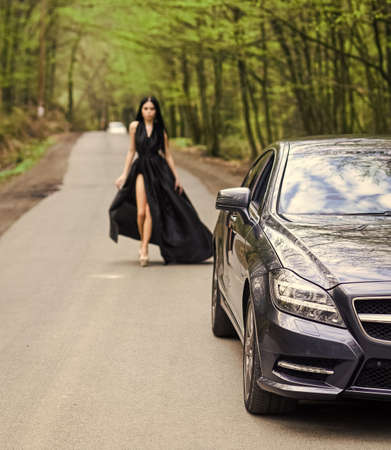 Driver girl. Beauty and fashion. Woman in black dress. Elegant lady escort service worker. Sexy girl elegant dress at road. Escort concept. Glamorous girl and luxury car. Escort and services