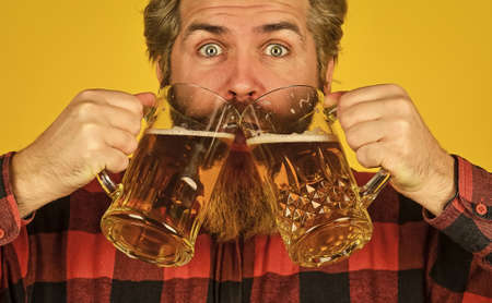 Brutal bearded male drinks beer from glass. Beer pub. Stylish bartender or barman in bar. recreation. Man hold glass of beer. hipster at bar counter. having fun watching football