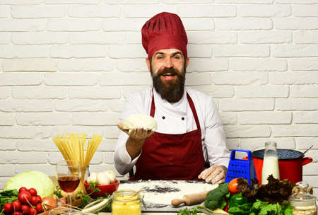 Cook with cheerful face in burgundy uniform sits by table