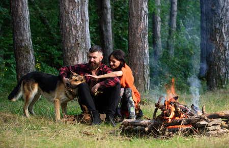 Man play, pat german shepherd dog near bonfire, nature background.
