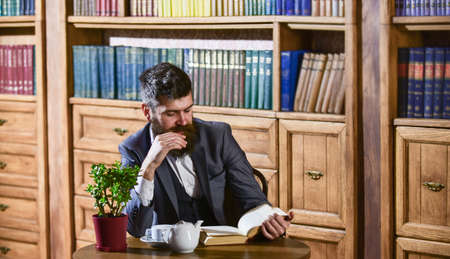 Aristocrat on thoughtful face reading book. Oldfashioned man near cup