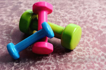Barbells in green, pink and cyan color on wooden surface