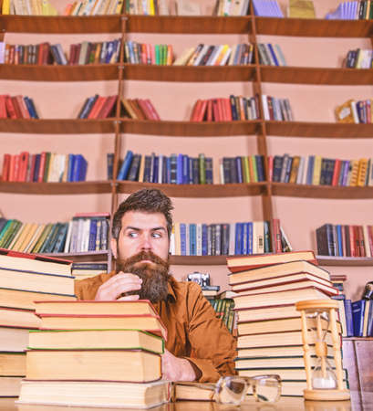 Teacher or student with beard sit at table with hourglass and glasses, defocused. Bookworm concept. Man on strict face sit between piles of books, while studying in library, bookshelves on background Reklamní fotografie