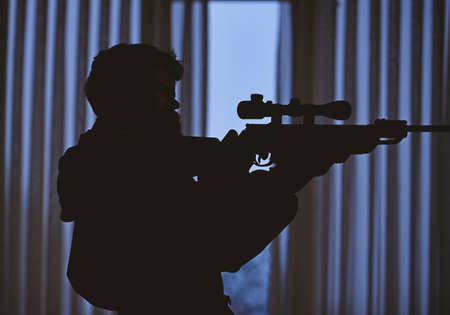 Silhouette of macho aiming at victim in front of window. Hunter, soldier with gun aiming before shooting. Shooter concept. Man unrecognizable with gun, rifle in dark interior background