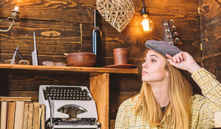 Girl in casual outfit with kepi in wooden vintage interior. Tomboy concept. Lady on calm face in plaid clothes looks cute and casual. Girl tomboy spend time in house of gamekeeper
