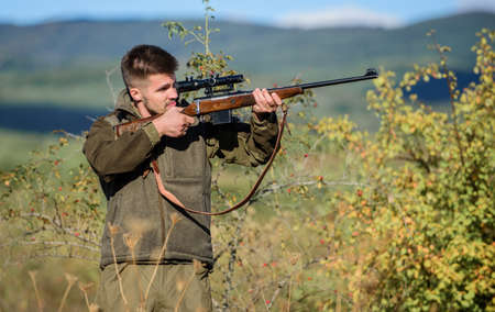 Hunter hold rifle. Hunting permit. Bearded hunter spend leisure hunting. Hunting equipment for professionals. Hunting is brutal masculine hobby. Man aiming target nature background. Aiming skills Stock Photo