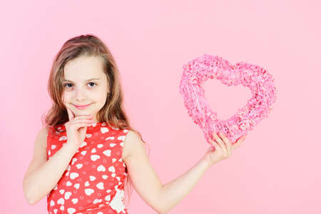 Valentine and valentines day celebration. Happy girl holding rosy heart on pink background. Romantic love concept. Sweetheart child with long hair smiling in red dress. Kindness and tenderness