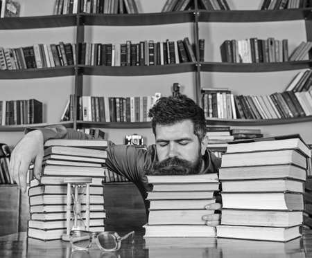 Man on sleeping face lay between piles of books, fall asleep while studying in library, bookshelves on background. Overstudied concept. Teacher or student with beard fall asleep on books, defocused Reklamní fotografie